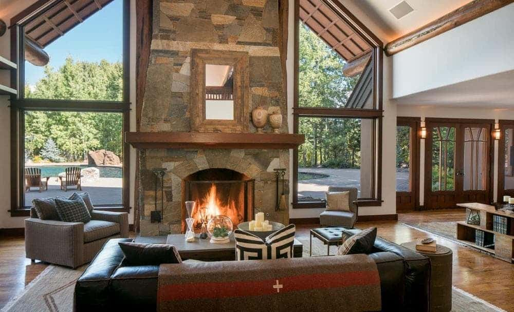 This charming and homey living room is dominated by the large stone structure that houses the large fireplace across from the comfortable black leather sofa. Images courtesy of Toptenrealestatedeals.com.