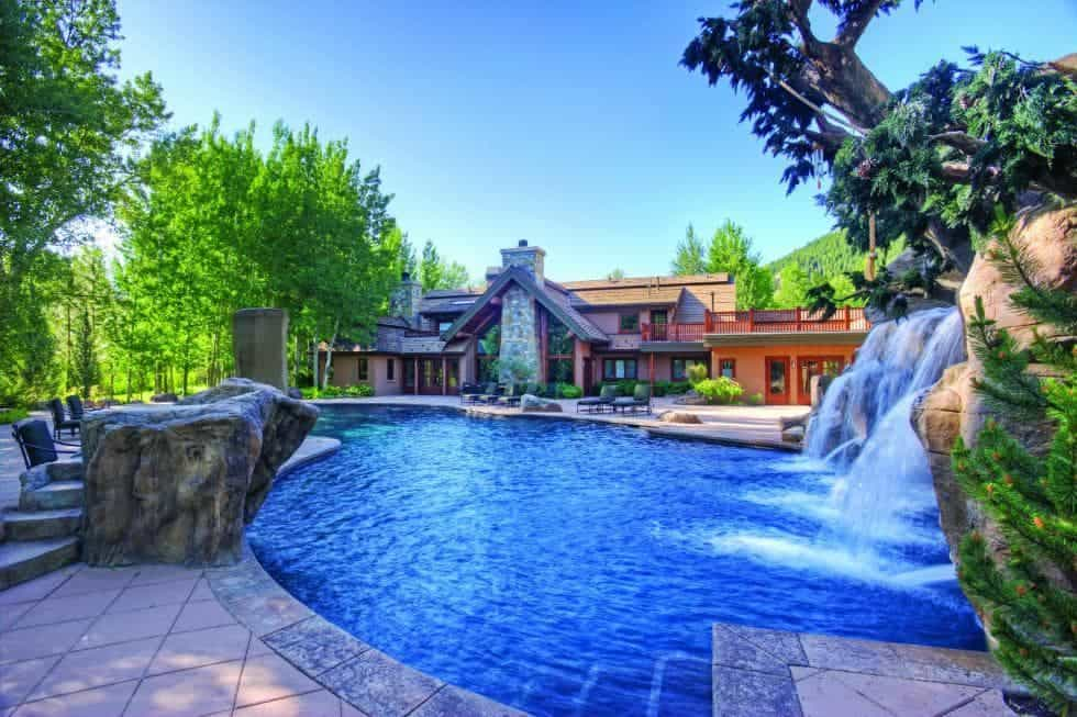From this vantage point of the back of the house, you can see the beautiful stone and wood structures of the house at the other side of the large pool of the backyard. Images courtesy of Toptenrealestatedeals.com.