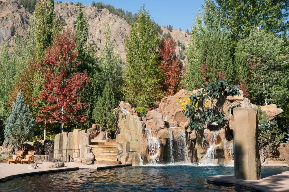 The large pool at the back of the house is complemented by the huge decorative rocky structure at the edge with natural-looking falls and tall trees in the background. Images courtesy of Toptenrealestatedeals.com.