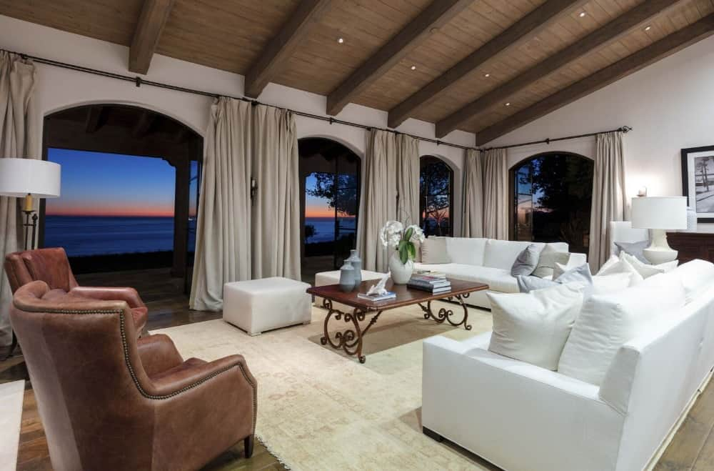 Another view of the formal living room showcasing its white walls and a tall wooden vaulted ceiling. Images courtesy of Toptenrealestatedeals.com.