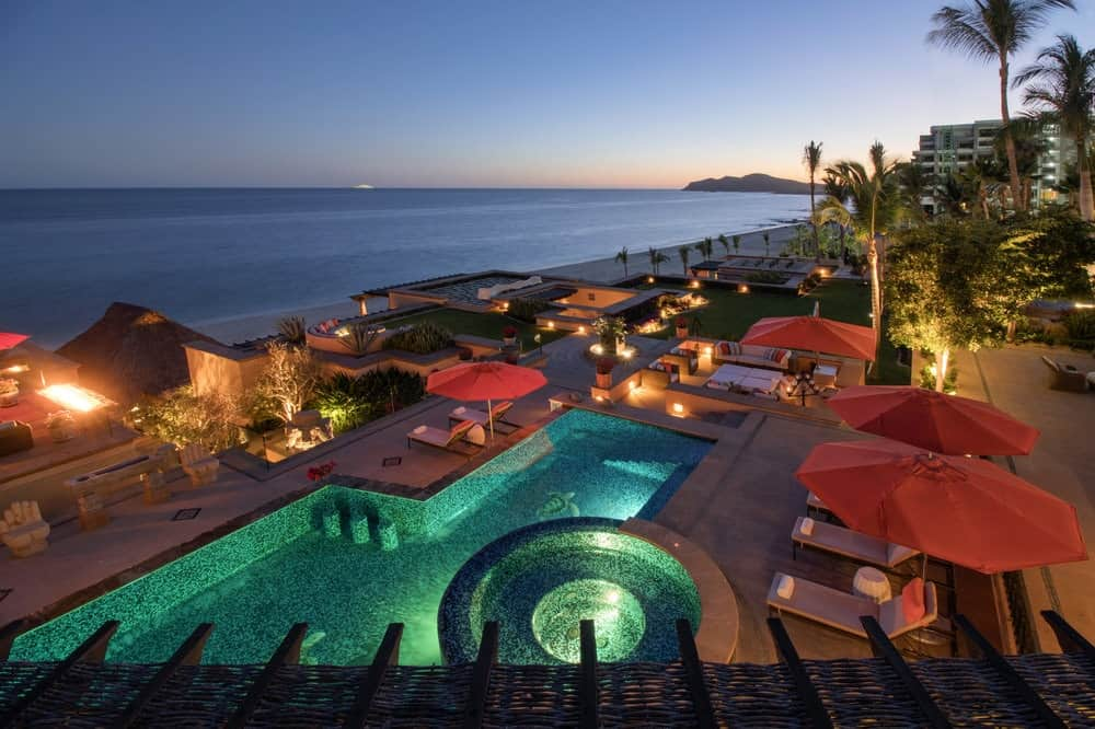 This is a top view of the gorgeous backyard pool that has a jacuzzi-type pool attached to it. This night time view shows the ethereal glow of the pool augmented by the warm and welcoming lights all around the outdoor area. Images courtesy of Toptenrealestatedeals.com.