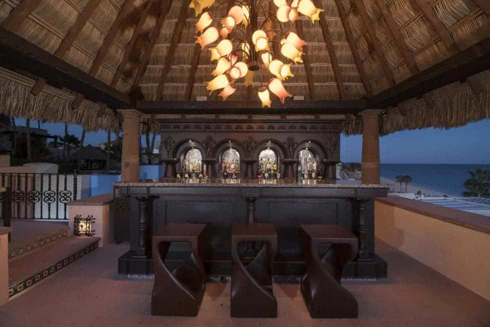 This is one of the estate's many bars. This one has an elegant dark wooden bar topped with multiple decorative pendant lights hanging from the arched wooden ceiling designed to feel like a tropical hut. Images courtesy of Toptenrealestatedeals.com.
