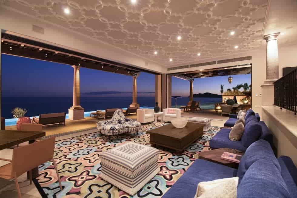 This is a luxurious living room with wide open walls that offers a sweeping view of the ocean. The pair of comfortable sofas are paired with a lovely dark wooden coffee table on a patterned colorful area rug. Images courtesy of Toptenrealestatedeals.com.