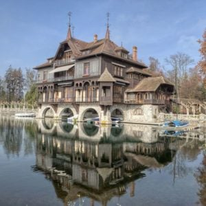 This is the lakeside front of the house with earthy wooden exterior walls and roofs. From this angle, you can see that a part of the house sits over the lake supported by concrete arches that create a perfect space for the boats underneath. Images courtesy of Toptenrealestatedeals.com.