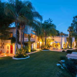The gorgeous home has wide open walls that spill warm welcoming yellow light onto the lush green lawn of grass surrounded by tall tropical trees complemented by outdoor lighting. Images courtesy of Toptenrealestatedeals.com.