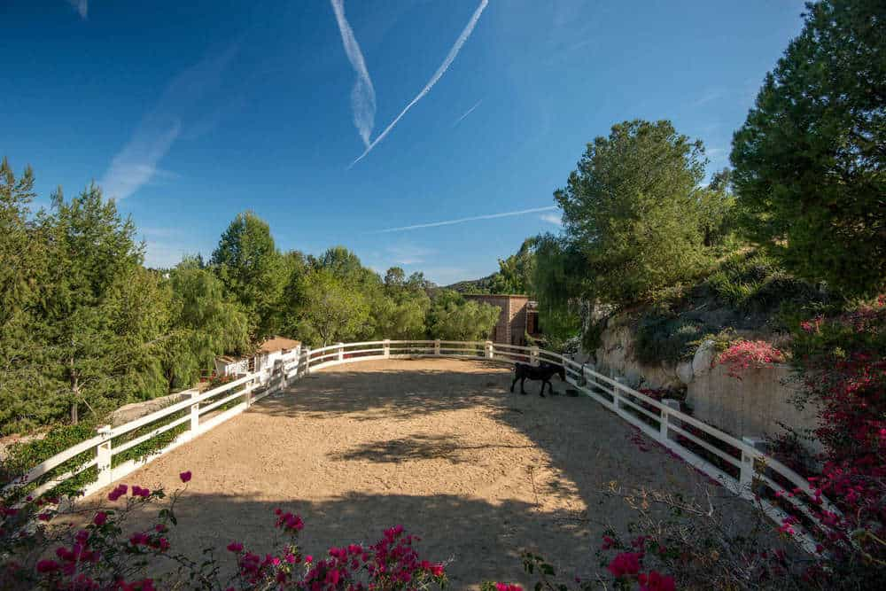 This is the horse enclosure of the equestrian center of the estate grounds with white wooden fences and tall surrounding trees. Images courtesy of Toptenrealestatedeals.com.