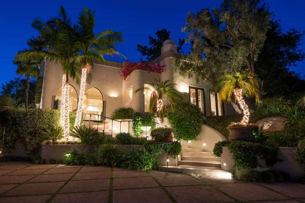 This view of the front of the house shows the gorgeous landscaping of tall tropical trees that are augmented by their spot lights. These adds to the charm of the beige exteriors festooned with arches. Images courtesy of Toptenrealestatedeals.com.