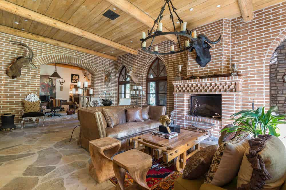 The charming and rustic red brick walls of this living room is complemented by the wooden ceiling exposed wooden beams and hangs a round chandelier over the wooden coffee table next to the fireplace. Images courtesy of Toptenrealestatedeals.com.