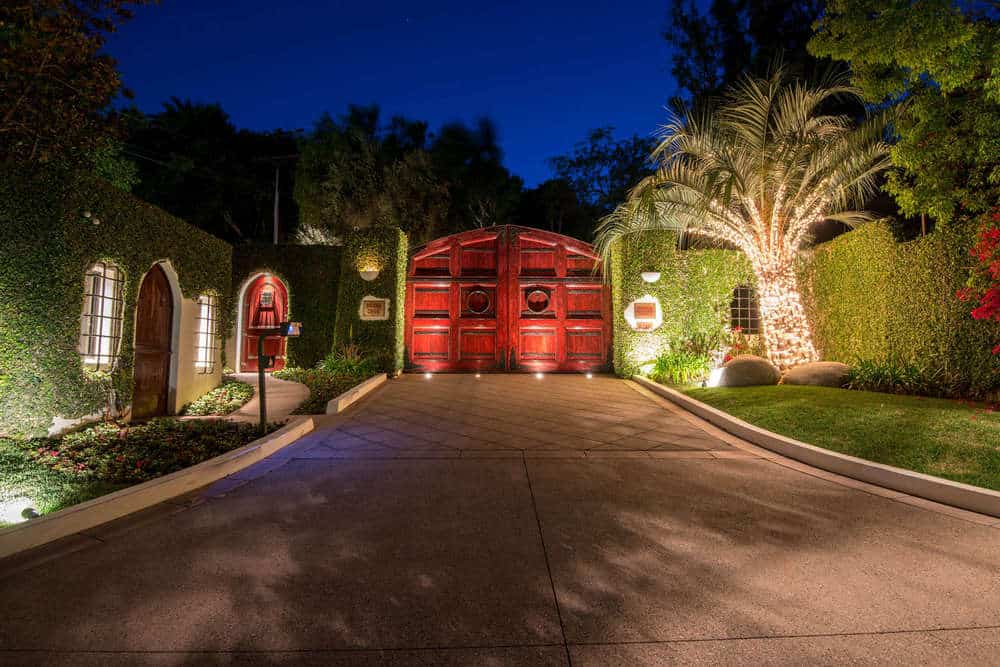 A wide driveway leads to the gorgeous main gate of the estate has a deep red color that stands out with the yellow spotlights that also makes the tropical trees glow. Images courtesy of Toptenrealestatedeals.com.