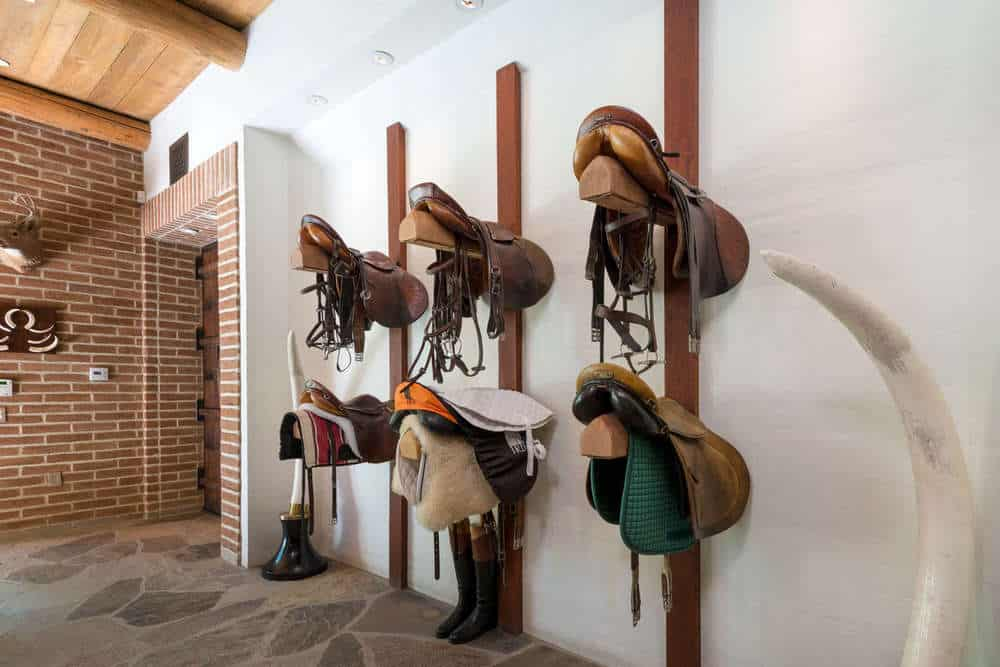 Before the entry of the equestrian center, there is a rustic mudroom that stores the saddles, boots and hats on wall-mounted wooden structures. Images courtesy of Toptenrealestatedeals.com.