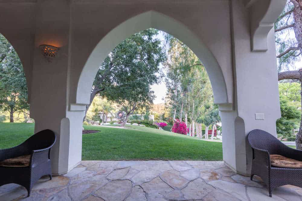 This is the area at the side of the house with a covered patio dominated by rows of elegant arches paired with wall-mounted lamps and comfortable cushioned arm chairs. Images courtesy of Toptenrealestatedeals.com.