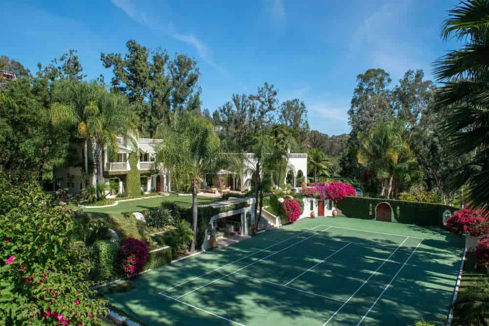 This is the charming green tennis court surrounded by lush green landscaping with vibrant flowers and tall tropical trees. Images courtesy of Toptenrealestatedeals.com.