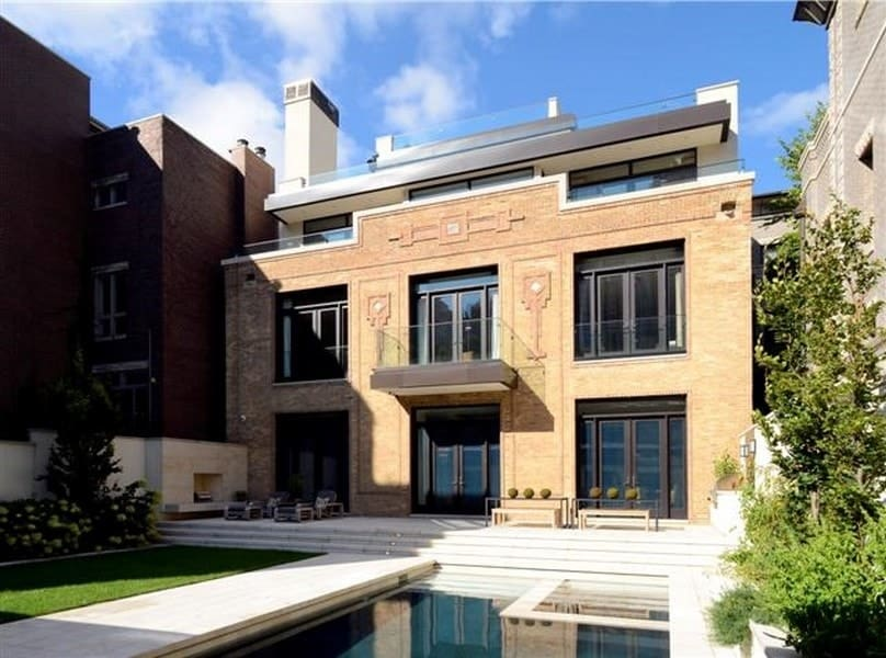 This repurposed electric substation retains most of its Art Deco facades and beige exterior walls as can be seen from this back view of the mansion filled with large glass windows and doors looking over the beautiful backyard that has a pool and a lawn of grass. Images courtesy of Toptenrealestatedeals.com.