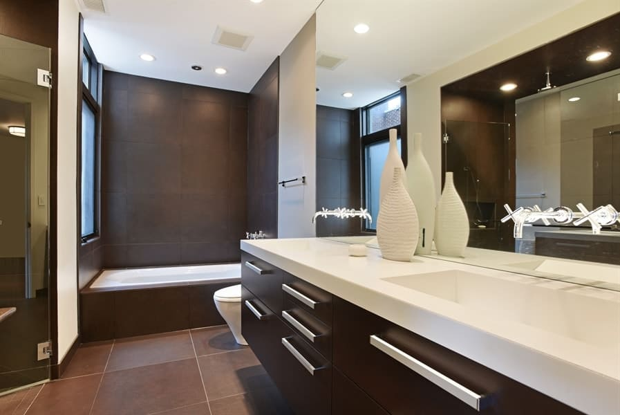 This other bathroom has a dark brown floating modern vanity to match the dark brown walls of the shower area and the housing of the bathtub contrasted by the bathtub and the toilet beside it. Images courtesy of Toptenrealestatedeals.com.