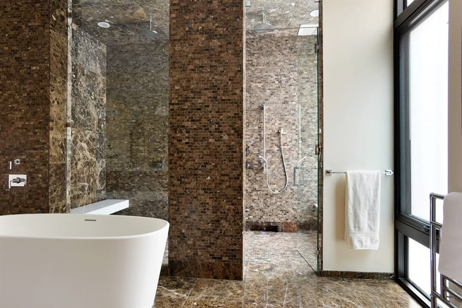 This bathroom has beautiful earthy marble floor and walls that are complemented by the glass walls of the shower area as well as the frosted glass window for privacy. Images courtesy of Toptenrealestatedeals.com.