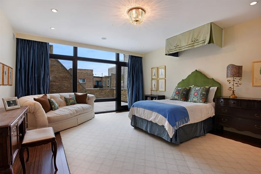 This is the primary bedroom with a large bed that has a cushioned headboard to stand out against the beige wall and matching ceiling brightened by the glass wall and door leading to the small balcony. Images courtesy of Toptenrealestatedeals.com.