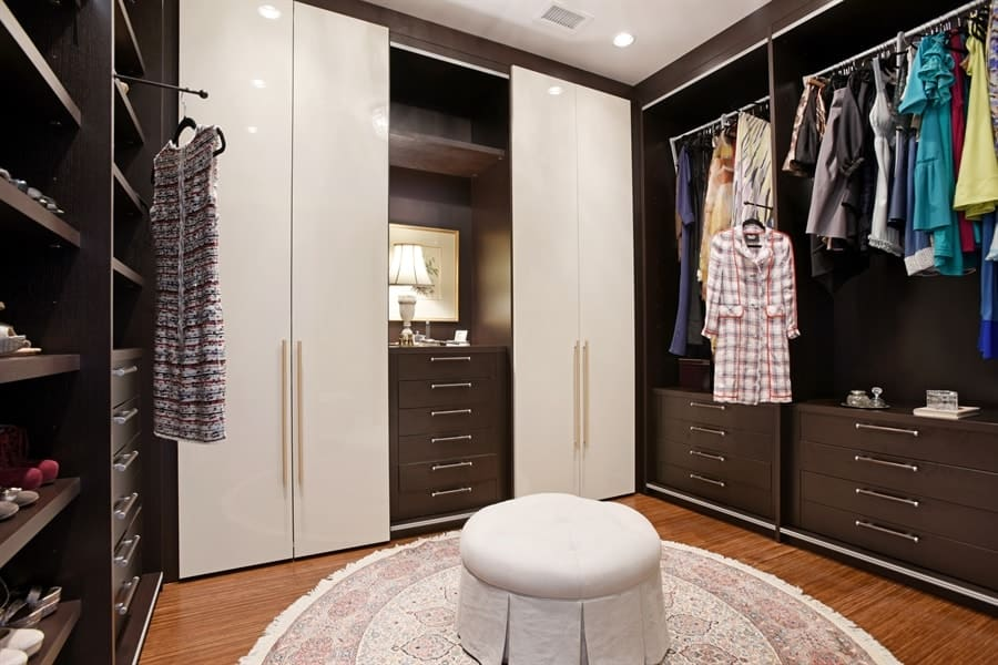 The lovely and spacious walk-in closet has large wooden structures lining the walls with racks, cabinets and drawers surrounding a small cushioned ottoman on a round area rug. Images courtesy of Toptenrealestatedeals.com.