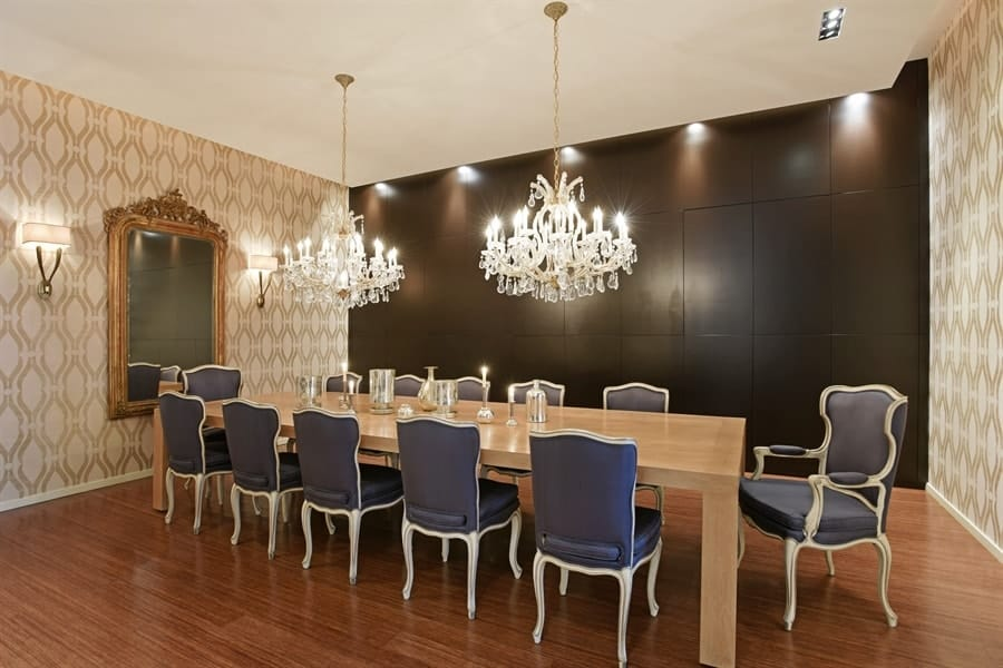 This formal dining room is dominated by the grogeous pair of crystal chandeliers that stands out against the black wall. These hang over a large wooden dining table surrounded by gray cushioned chairs. Images courtesy of Toptenrealestatedeals.com.