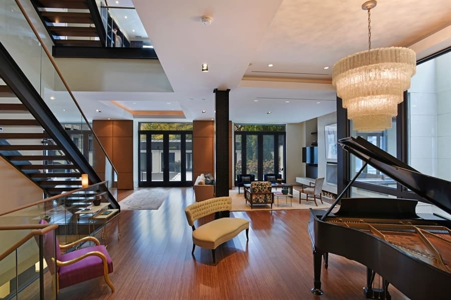 This is a great room that houses the living room on the distance and a music area that has a grand piano on the corner paired with a few comfortable chairs on an open area topped with a crystal chandelier. Images courtesy of Toptenrealestatedeals.com.