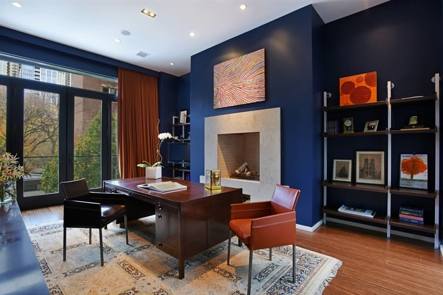 The gorgeous deep blue walls of this home office makes the fireplace stand out across from the charming dark wooden desk on a patterned area rug. Images courtesy of Toptenrealestatedeals.com.