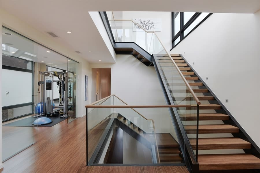 This is the second floor landing with a nice view of the stair case bordered with glass to complement the metal frame of the stairs and wooden steps that match the hardwood flooring. Images courtesy of Toptenrealestatedeals.com.