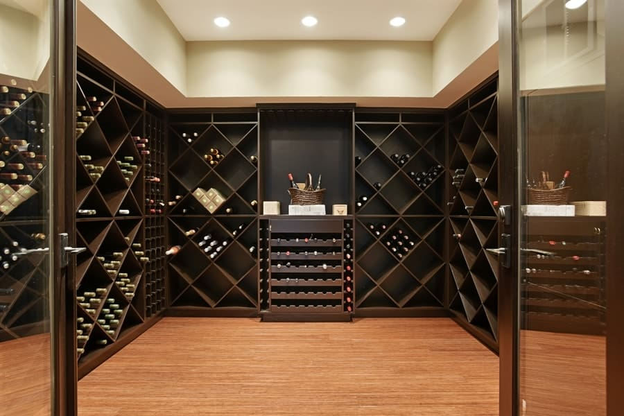 This is the charming wine celar with walls dominated by the dark wooden structures for wine storage paired with a hardwood flooring and a tall beige ceiling. Images courtesy of Toptenrealestatedeals.com.