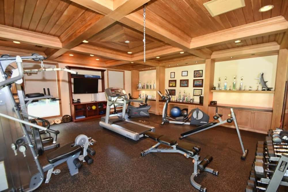 Large and properly equipped home gym with stylish flooring and has a TV on the wall. Images courtesy of Toptenrealestatedeals.com.