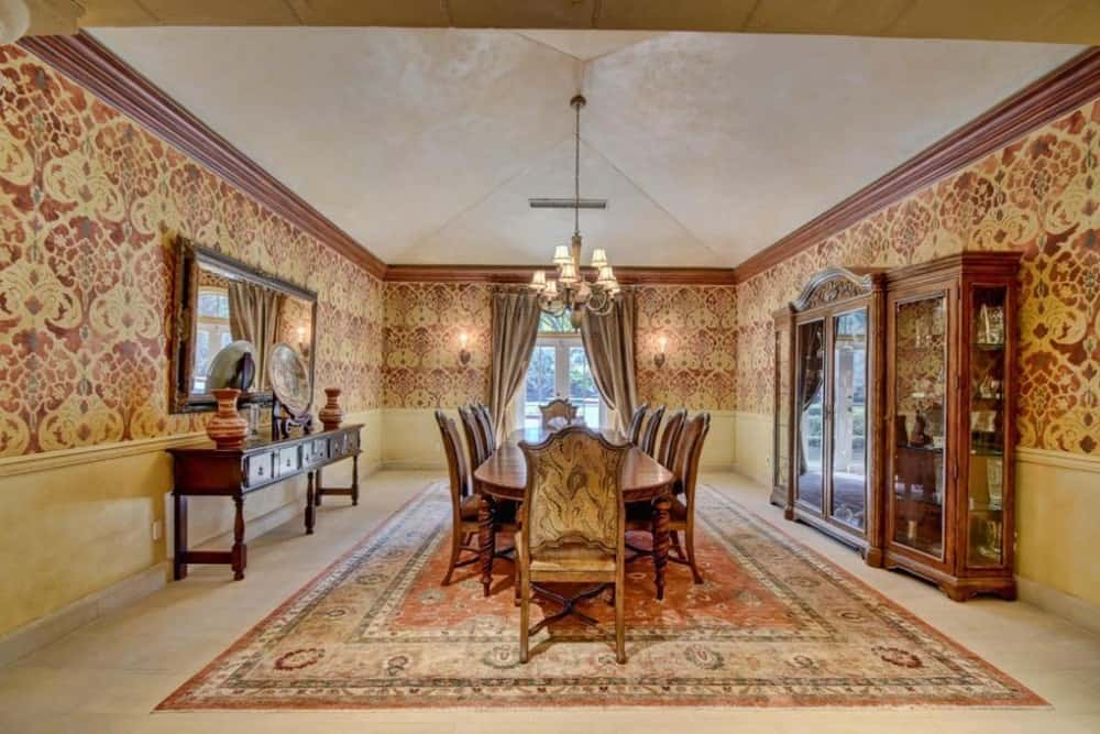 A formal dining room with elegant walls and a large area rug where the dining table and chairs are set. Images courtesy of Toptenrealestatedeals.com.
