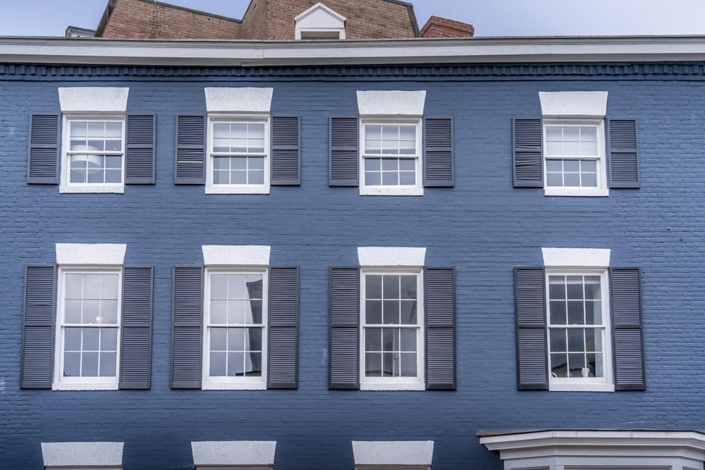 Facade of a luxury colonial Georgian style townhouse with symmetric double pan shutter windows and blue-painted brick exterior.