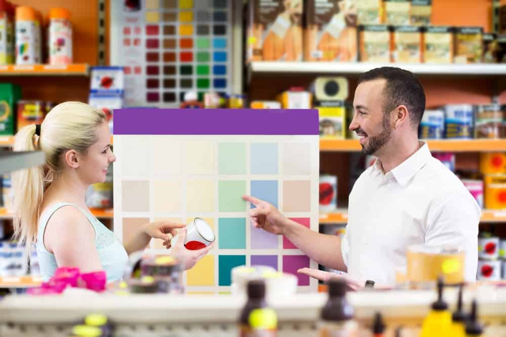 A woman and a man choose among the color samples in a shop.