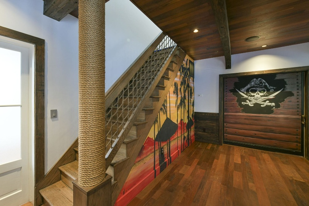 The entry foyer of the house features hardwood flooring and a pirate-themed straight staircase. Images courtesy of Toptenrealestatedeals.com.