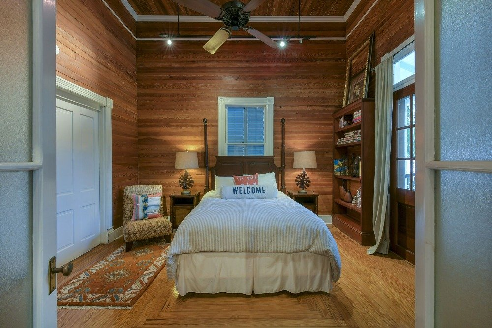 A bedroom with a tall ceiling, hardwood floors and wooden walls. There's a built-in shelf on the side. Images courtesy of Toptenrealestatedeals.com.