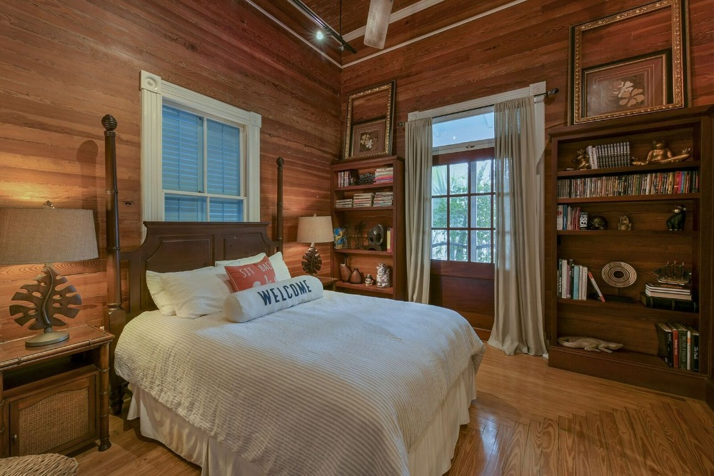 A bedroom featuring a tall ceiling and wooden walls, along with hardwood flooring. There are built-in shelving on the side of the room. Images courtesy of Toptenrealestatedeals.com.