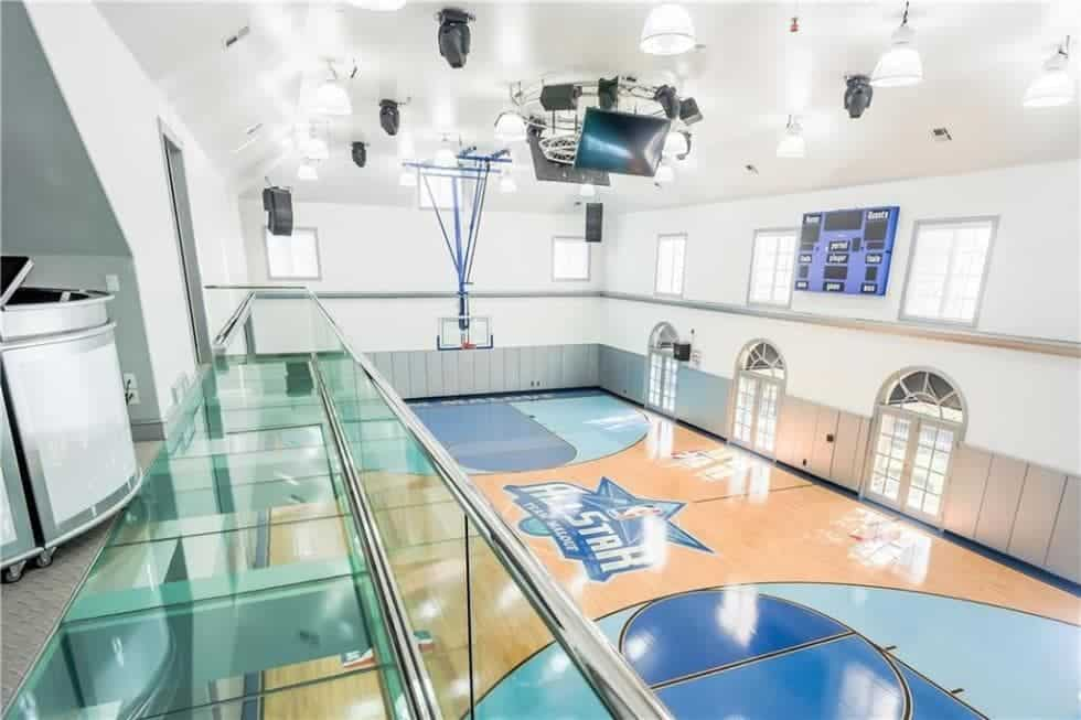 This is the indoor basketball court of the massive estate large enough to fit this professional-size court with massive screens at the tall ceiling along with modern lighting. Images courtesy of Toptenrealestatedeals.com.