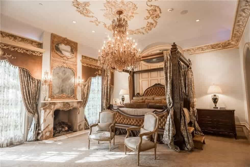 The four-posted bed of the primary bedroom is adorned with curtains and a warm elegant fireplace on the side that matches the aesthetic of the massive chandelier hanging over the two arm chairs at the foot of the bed. Images courtesy of Toptenrealestatedeals.com.