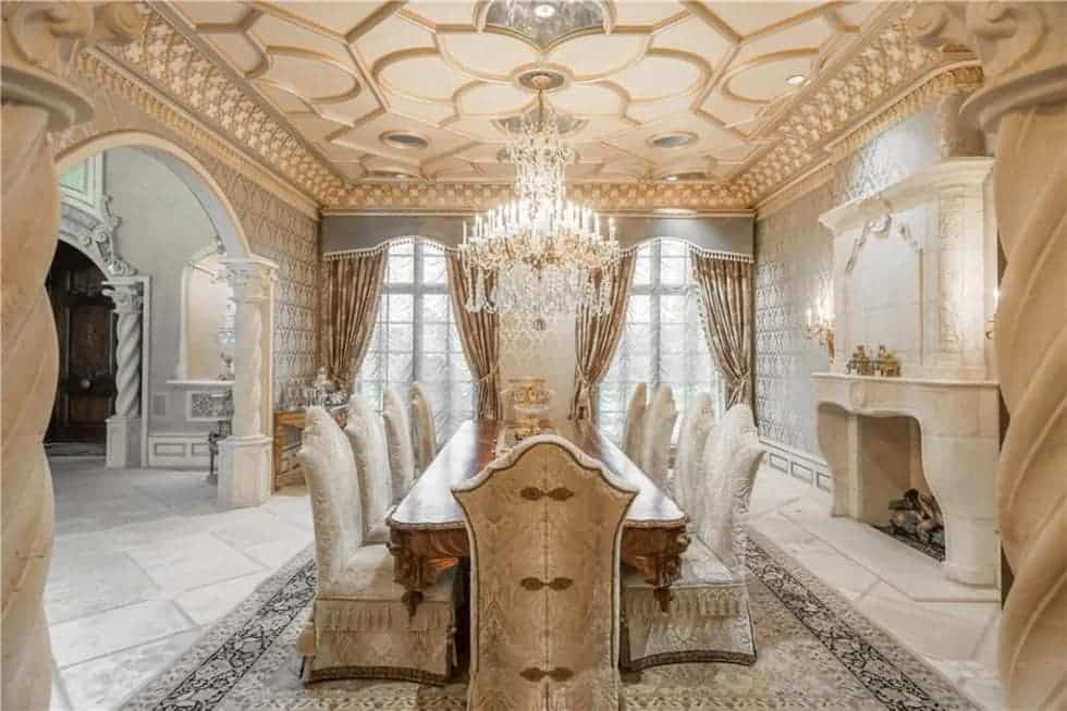 This formal dining room has an elegant accented ceiling that hangs a majestic chandelier over the large wooden dining table with a gorgeous fireplace on the side. Images courtesy of Toptenrealestatedeals.com.