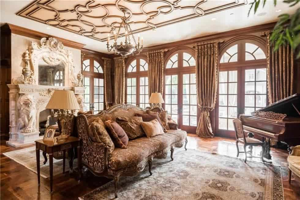 This living room has tall arched windows on one side bringing in an abundance of natural lighting to the brown sofa that matches the accents of the ceiling complemented and warmed by the white-mantled fireplace on the other side of the room from the piano. Images courtesy of Toptenrealestatedeals.com.