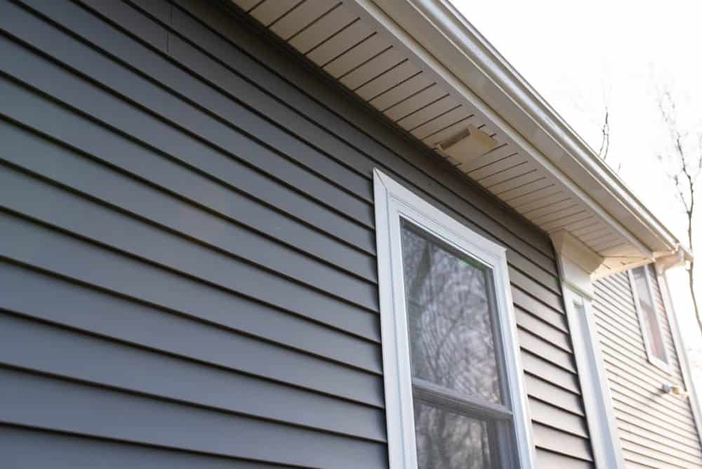 Close up of a house exterior's dark gray vinyl siding.