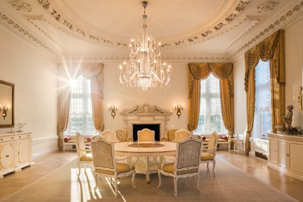 This dining room has a smaller space and fewer chairs for a more intimate dining experience. The beige circular dining table is topped with a majestic chandelier that hangs from the cove beige ceiling. These are also a perfect match for the beige dining chairs as well as the Victorian-style fireplace on the far wall that is flanked by two tall curtained windows. Images courtesy of Toptenrealestatedeals.com.