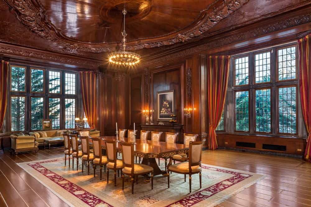 This large formal dining room is perfect for a large group. It has elegant dark brown walls and ceiling that works perfectly with the warm yellow lights of the circular chandelier that matches with the wall-mounted lamps. The large rectangular dining table also matches the tone of the walls surrounded by wooden chairs that has beige cushions to pair with the large beige patterned area rug underneath. These are all complemented by the large glass windows that bring in an abundance of natural lighting. Images courtesy of Toptenrealestatedeals.com.