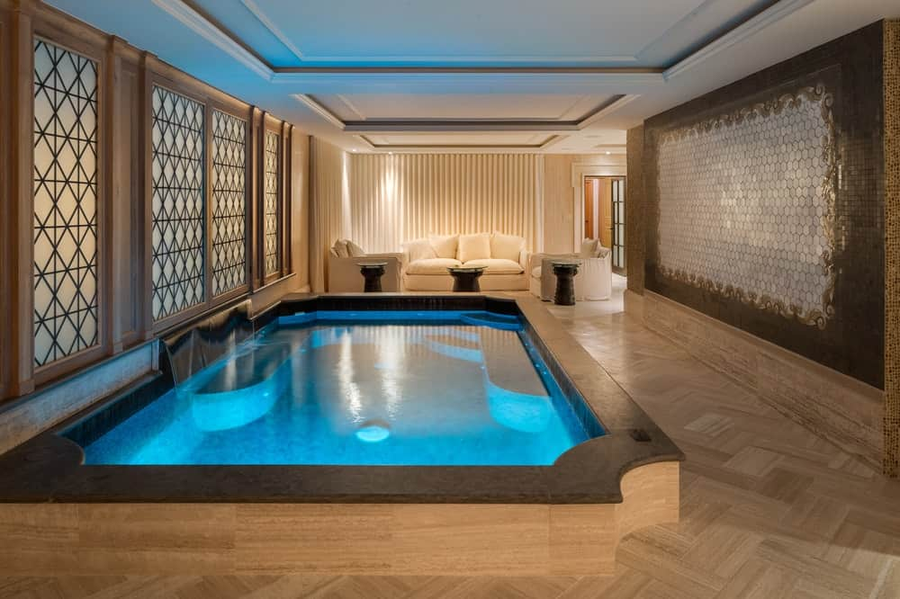The huge mansion also has an indoor pool and spa with its own lighting making it glow a brilliant blue against the beige area. At the far end is a comfortable sitting area and living room fitted with a beige cushioned sofa set paired with dark side tables. Images courtesy of Toptenrealestatedeals.com.