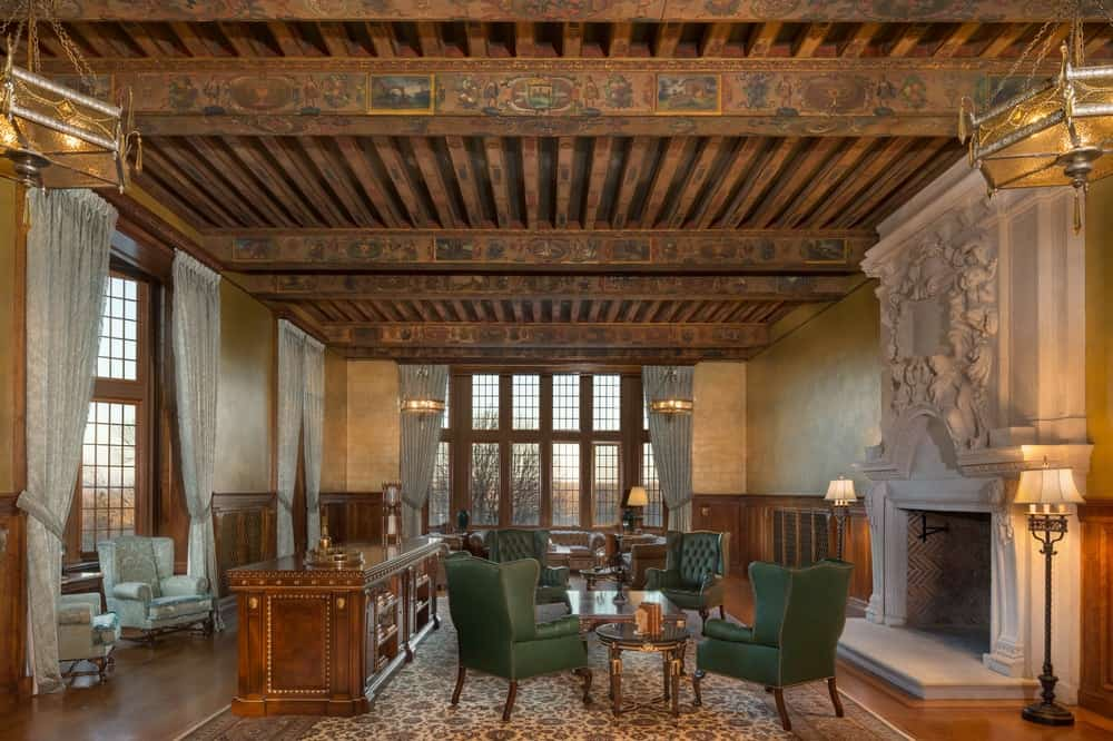 This is a large charming living room with enough space for two areas underneath the rustic wooden ceiling filled with exposed wooden beams that has artistic images on them. The living room area by the large window on the far side has luxurious brown leather sofas while the other area has four green cushioned arm chairs next to a large Victorian-style stone fireplace adorned with a large stone carving with elegant designs. Images courtesy of Toptenrealestatedeals.com.