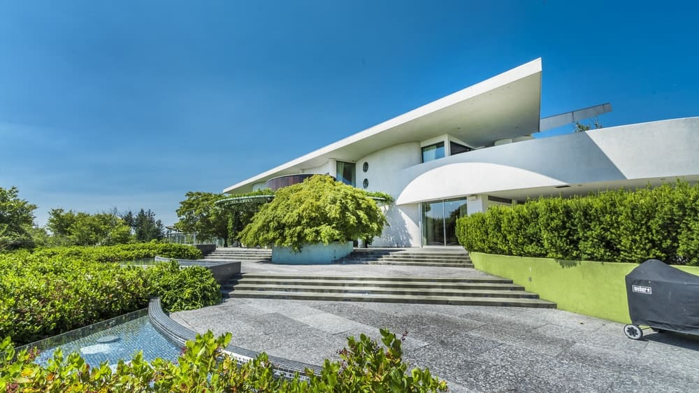 This view of the front of the house shows the beautiful white modern exteriors of the house complemented by the surrounding lush green landscaping that is filled with various shrubbery along with a large walkway of gray concrete with sets of steps leading to the main entry of the house. Images courtesy of Toptenrealestatedeals.com.