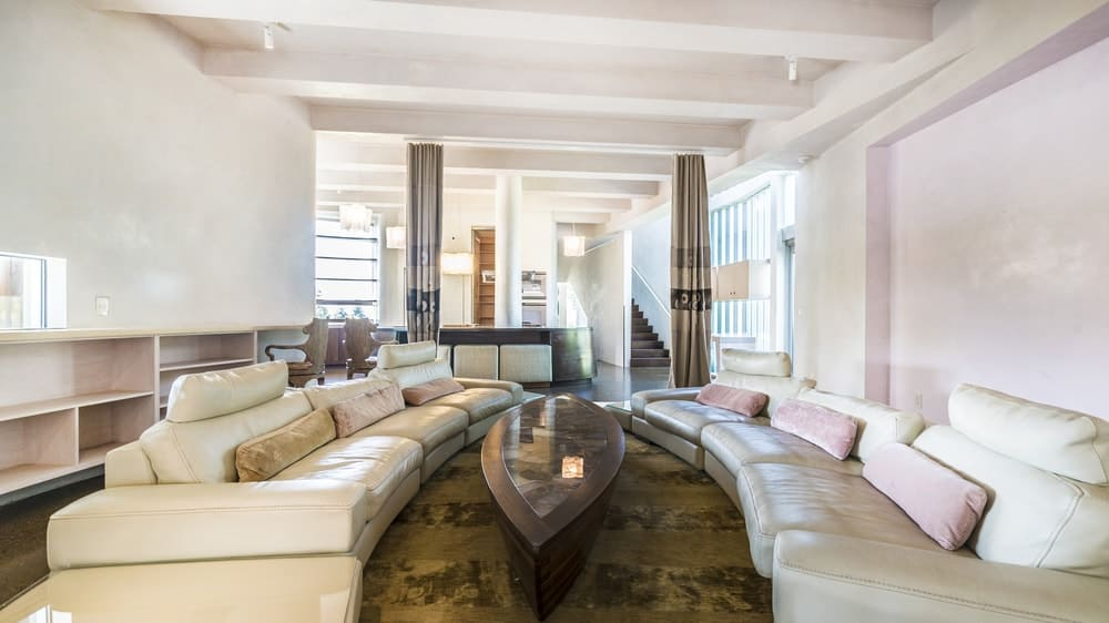 This charming living room has two sets of beige leather curved sectional sofas flanking a wooden coffee table customized to fit the shape of that the two sofas that match well with the light tones of the surrounding walls and ceiling that has exposed beams. Images courtesy of Toptenrealestatedeals.com.
