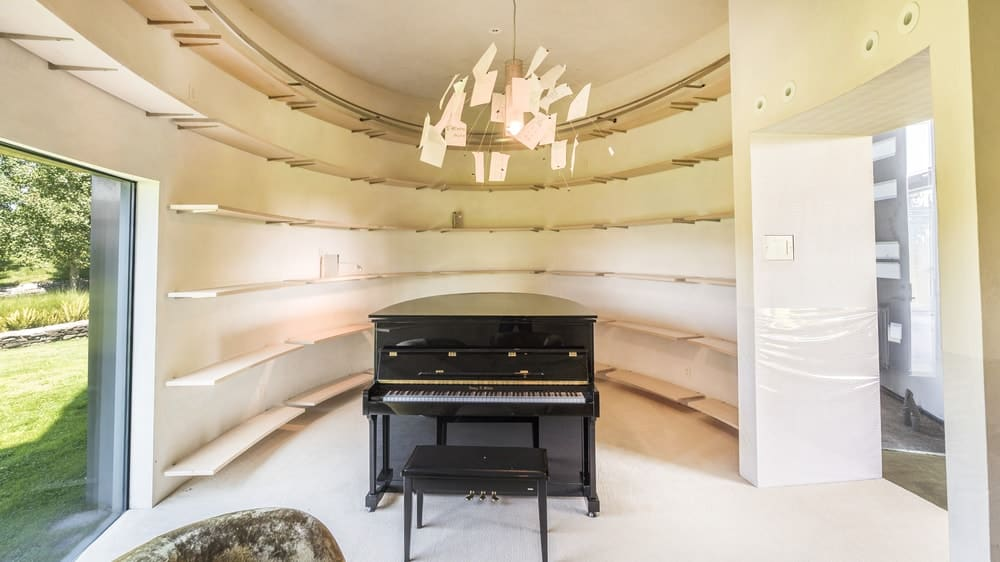 This is the music room with beige curved walls that has several layers of floating shelves making the black piano stand out in the middle that is topped with a decorative lighting adorned by pieces of paper. Images courtesy of Toptenrealestatedeals.com.