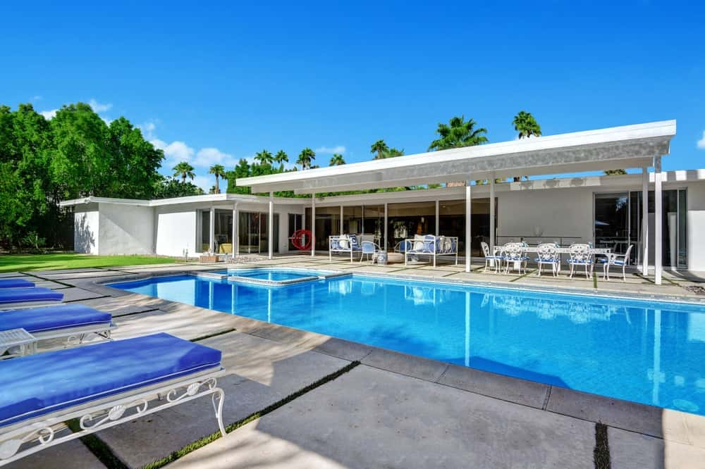 The lovely pool side of the back of the house has a large covered area with a patio sitting area on one side and an outdoor dining area on the other. Images courtesy of Toptenrealestatedeals.com.