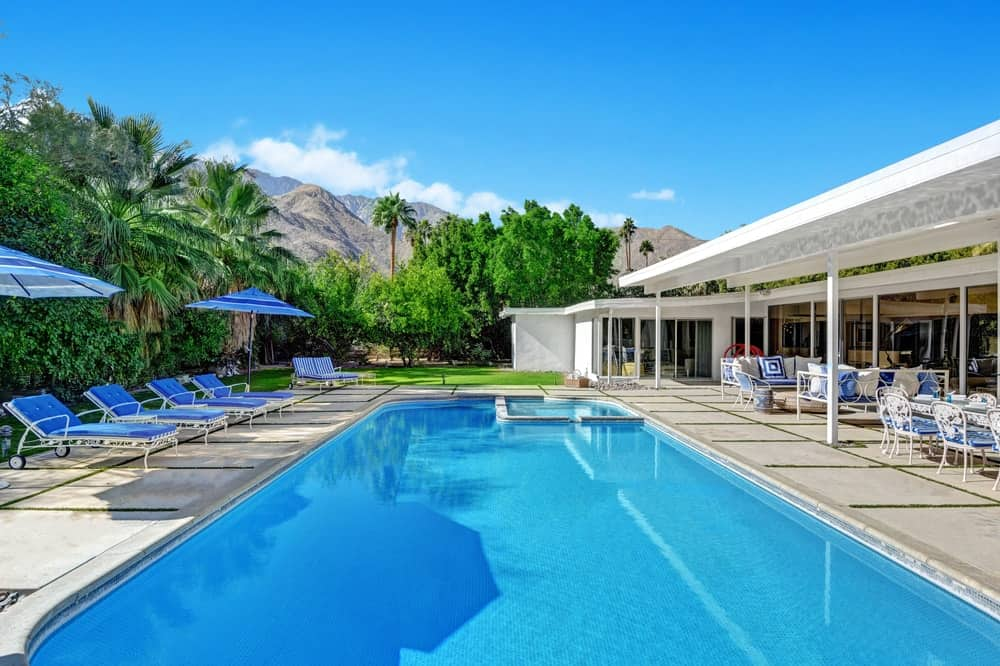 The beautiful swimming pool of the backyard is surrounded by concrete walkways and walled by lush landscaping for privacy. Images courtesy of Toptenrealestatedeals.com.