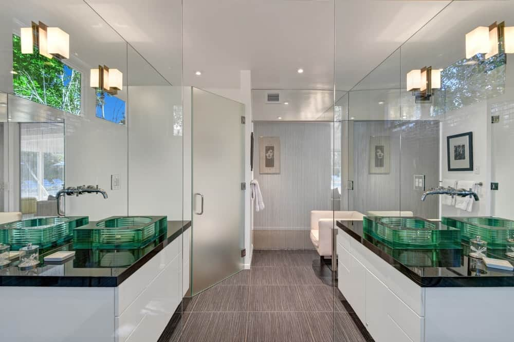 This beautiful bathroom has elements of glass all around with its shower area frosted glass walls, wall-mounted mirrors and green glass sinks to its vanities. Images courtesy of Toptenrealestatedeals.com.