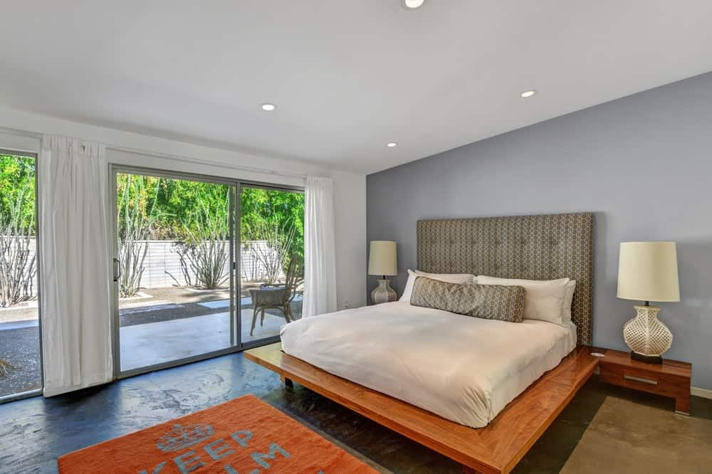 This bedroom has a large platform bed with a wooden frame that matches the area rug at the foot of the bed brightened by the sliding glass walls. Images courtesy of Toptenrealestatedeals.com.