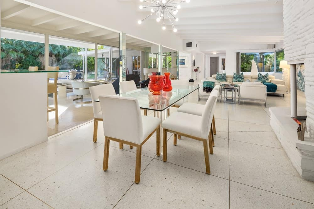 The white ceiling of the dining hangs a modern decorative chandelier over the glass-top dining table paired with cushioned seats. Images courtesy of Toptenrealestatedeals.com.